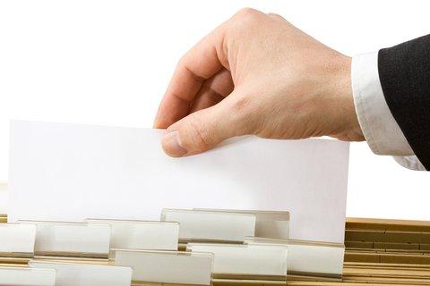 Ilustrační foto - Ruka úředníka sregistračním formulářem