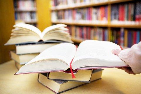 Ilustrační foto - otevřené knihy na stole vměstské knihovně