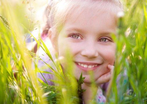 ilustrační foto - usměvavá holčička ležící vtrávě