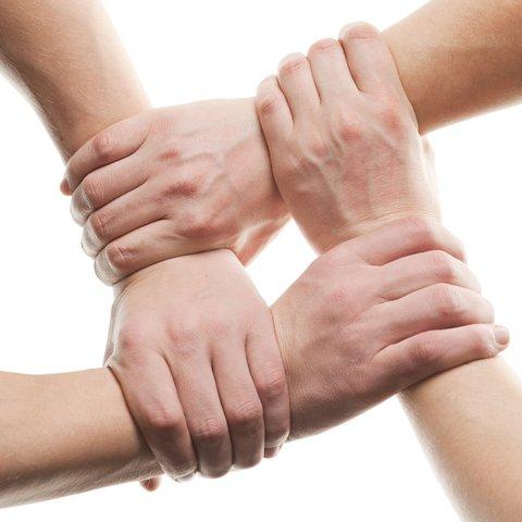 Ilustrační foto - Dva zkřížené páry rukou tvořící sedátko