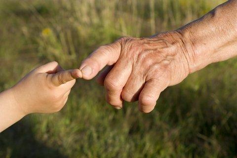Ilustrační foto - Ukazováček ruky starého člověka se dotýká ukazováčku ruky malého dítěte